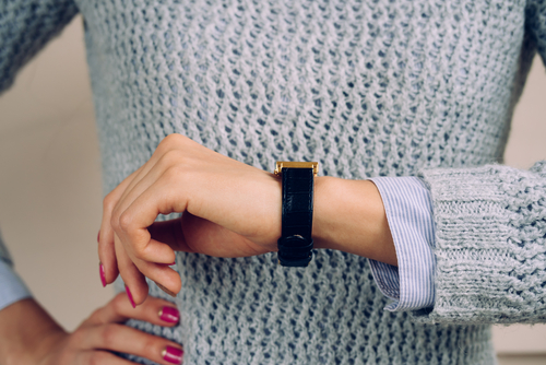Eine Dame, die ihre Uhr am linken Handgelenk trägt.