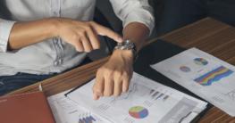 Mann im Hemd zeigt auf Armbanduhr
