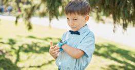 Kleiner Junge spricht in seine Smartwatch rein.