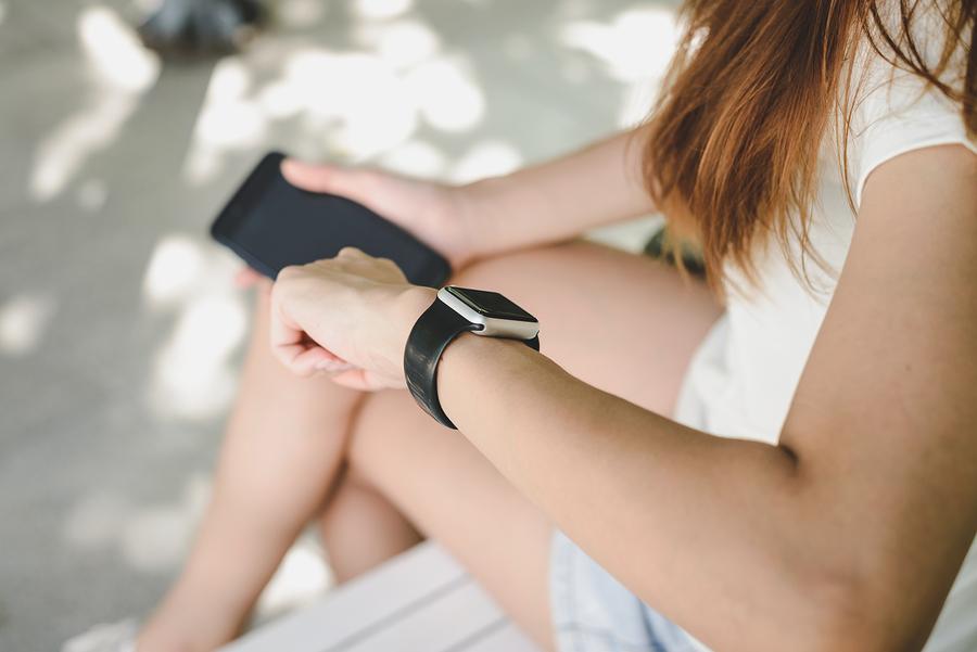 Frau hält Handy in der rechten Hand und benutzt Smartwatch am rechten Handgelenk.