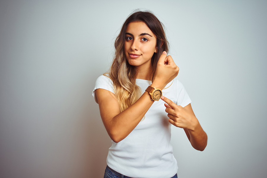 Young beautiful woman wearing casual white t-shirt over isolated background In hurry pointing to watch time, impatience, looking at the camera with relaxed expression