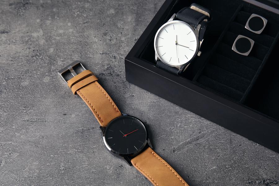 Braune Armbanduhr liegt vor Uhrenbox, schwarze Uhr befindet sich darin.