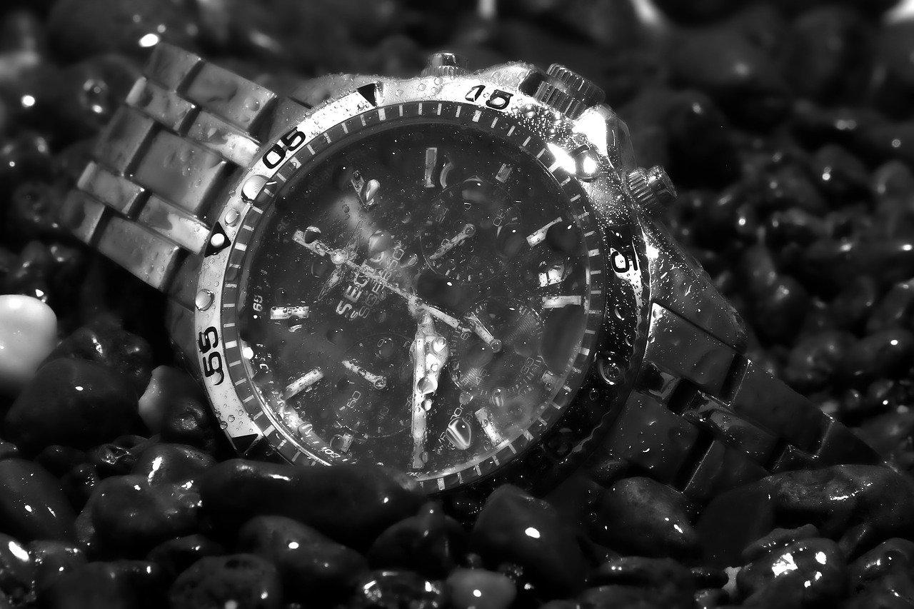 Nasse Armbanduhr liegt auf Kieselsteinen Ki