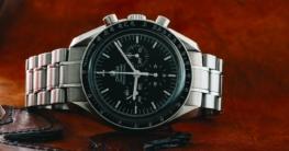 Eine Omega Speedmaster Armbanduhr liegt auf einem dunklen Holztisch