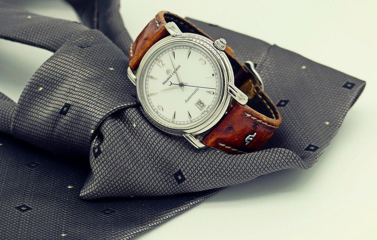 Armbanduhr liegt mit Krawatte auf dem Tisch