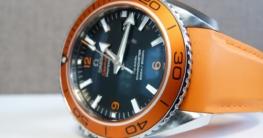 Orangene Omega Armbanduhr liegt auf der OVP